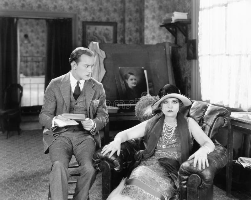 坐在客厅的男人和妇女读信和看起来惊奇(所有人被描述不是更长生存和不 库存照片