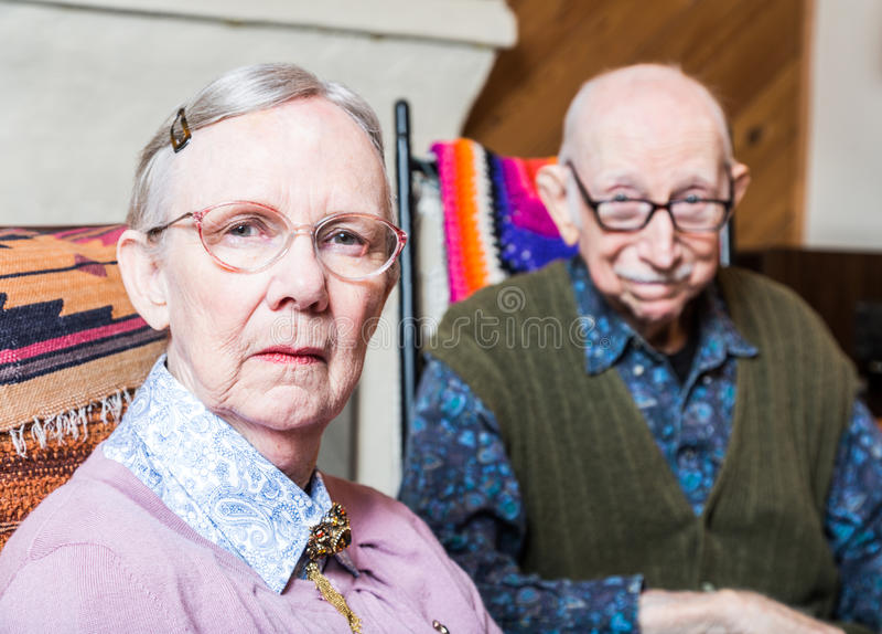 坐在客厅的老妇人和人 免版税库存照片