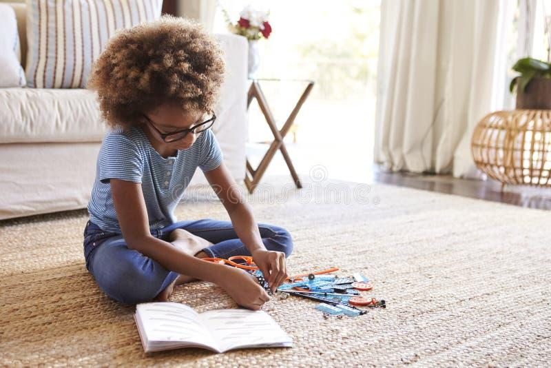 坐在客厅读的指示的地板和修建模型,关闭的青春期前的女孩  免版税库存照片