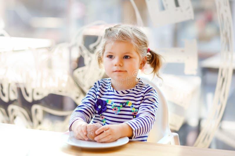 坐在室内咖啡馆餐馆的逗人喜爱的矮小的可爱的小孩女孩 吃面包或甜点的愉快的健康小孩子 免版税库存图片
