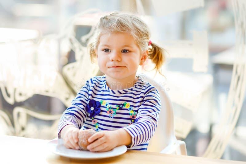 坐在室内咖啡馆餐馆的逗人喜爱的矮小的可爱的小孩女孩 吃面包或甜点的愉快的健康小孩子 库存图片