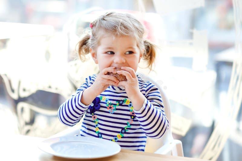 坐在室内咖啡馆餐馆的逗人喜爱的矮小的可爱的小孩女孩 吃面包或甜点的愉快的健康小孩子 库存照片