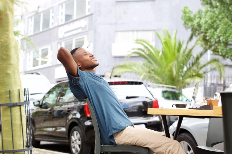 坐在室外咖啡馆的轻松的年轻非洲人 免版税库存照片
