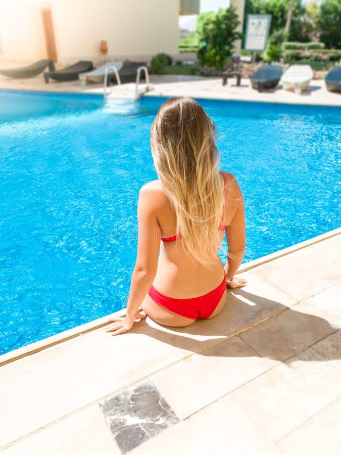 坐在室外游泳场旁边的性感的年轻女人的背面图图象 女孩放松和有美好时光在期间 库存照片