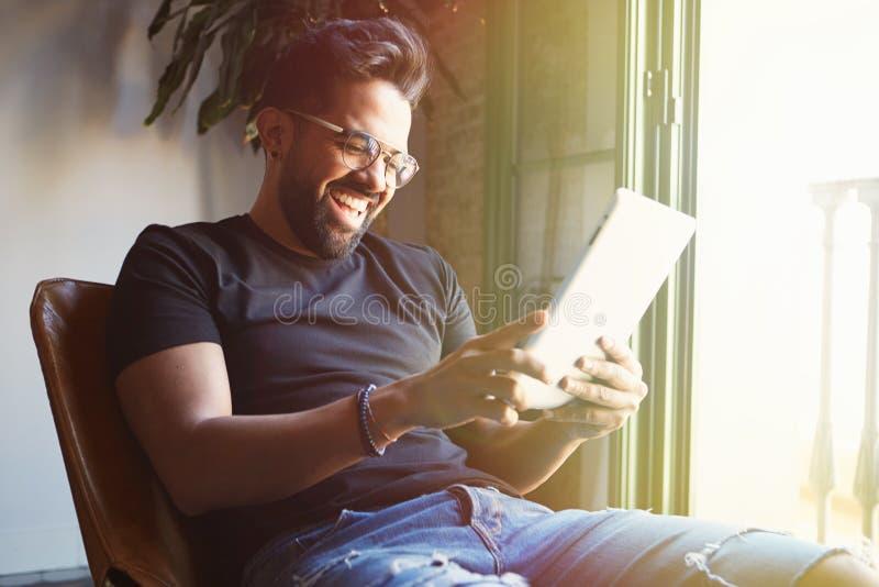 坐在家和使用数字式片剂的年轻愉快的有胡子的人为冲浪的网互联网 使用小配件的人在公寓 图库摄影