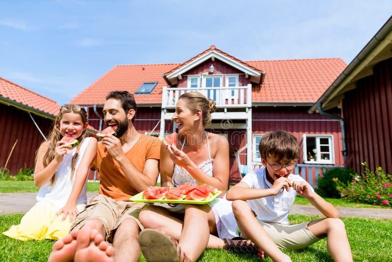 坐在家庭吃西瓜草前面的家庭  免版税库存照片