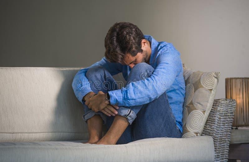 坐在家疲倦的和沮丧的沙发长沙发感觉被淹没的和担心的sufferi的年轻可爱和英俊的哀伤的拉丁人 库存图片