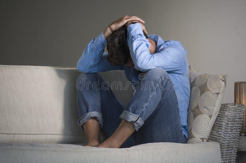 坐在家疲倦的和沮丧的沙发长沙发感觉被淹没的和担心的sufferi的年轻可爱和英俊的哀伤的拉丁人 图库摄影