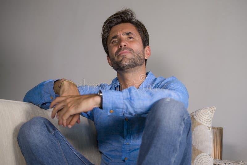 坐在家疲倦的和沮丧的沙发长沙发感觉被淹没的和担心的sufferi的年轻可爱和英俊的哀伤的拉丁人 免版税库存图片