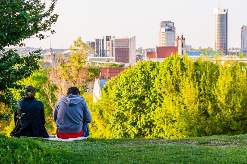 坐在小山的草草坪和看在城市地平线,都市风景的年轻人和妇女、朋友或者夫妇 免版税库存图片