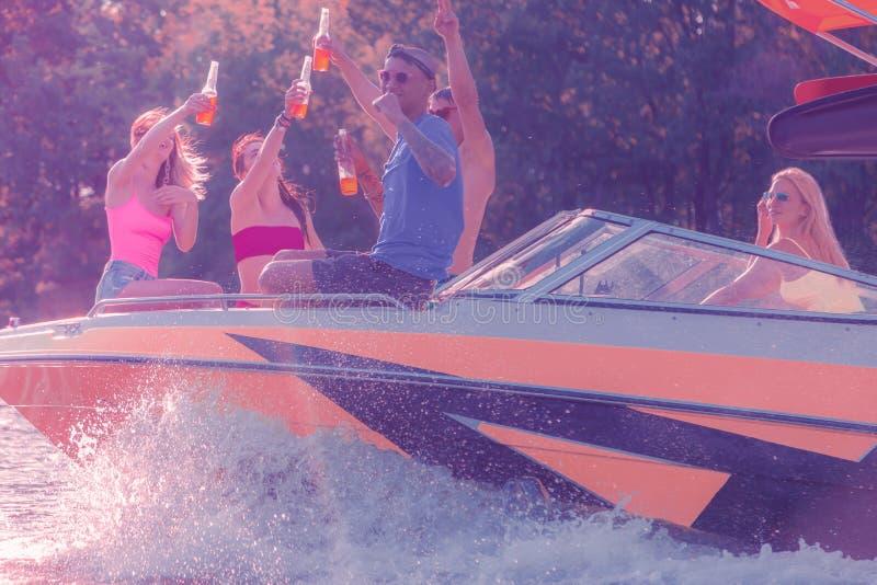 坐在小船的弓的快乐的公司 免版税库存图片