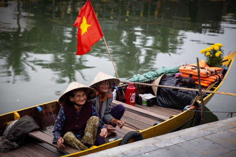 坐在小船的愉快的越南妇女 库存图片