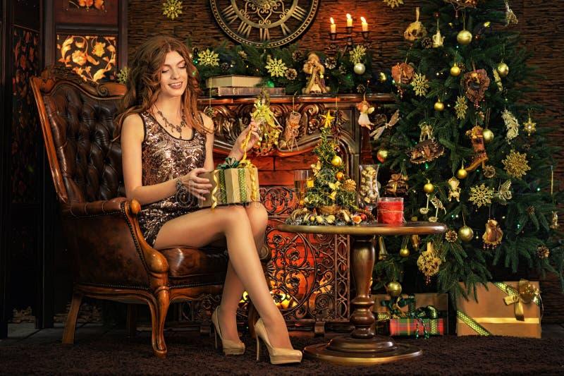 坐在屋子里的美丽的年轻女人画象装饰对圣诞节 库存照片