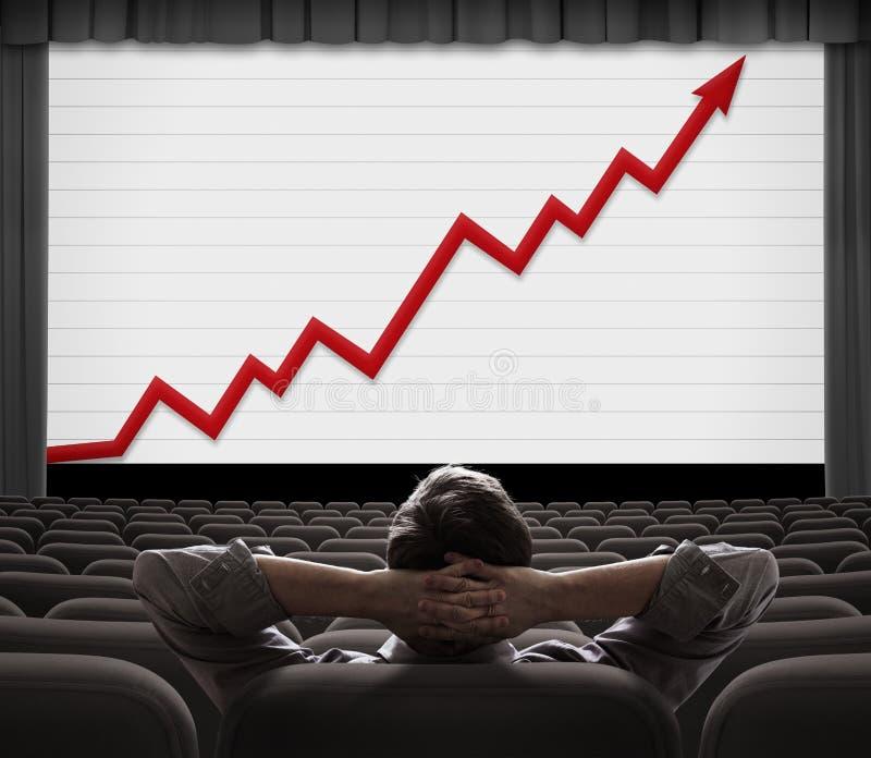 坐在屏幕上,看着屏幕,看着不断增长的财务图 图库摄影