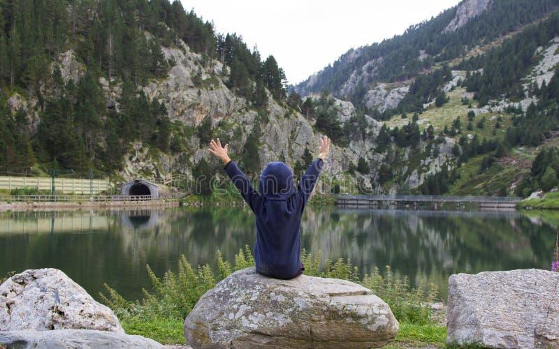 坐在岩石的孩子举悬而未决他的手和赞赏的山风景、冒险或者自由概念 免版税库存图片