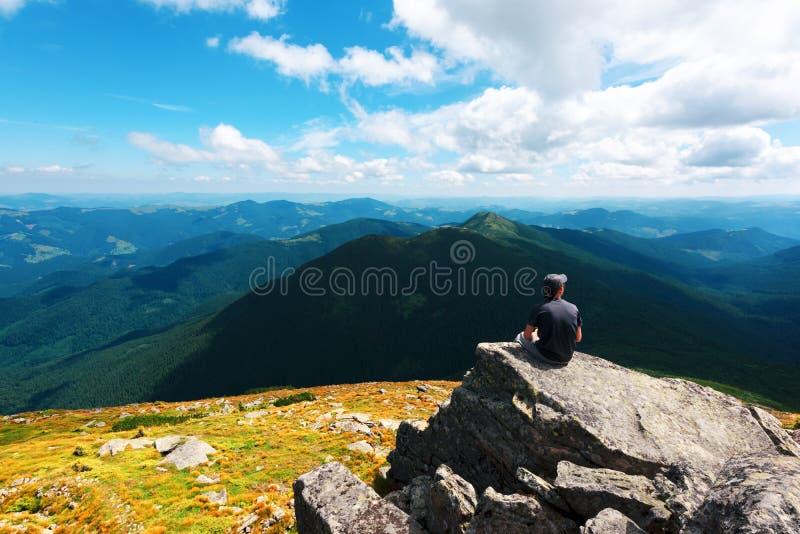 坐在峭壁边缘的一个孤立游人 免版税库存图片
