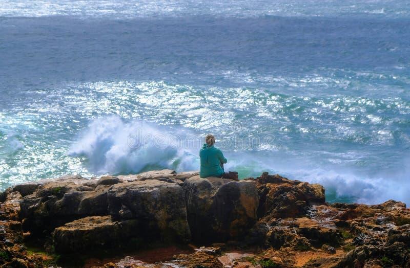 坐在峭壁边缘的女孩冥想强的wav 免版税库存图片