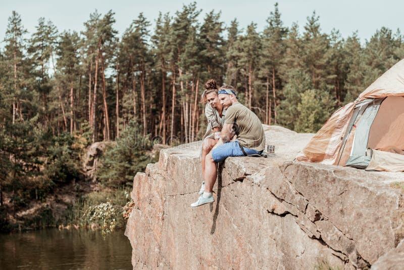 坐在峭壁边缘的背包徒步旅行者夫妇在湖附近在帐篷的夜以后 图库摄影