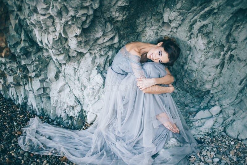 坐在峭壁附近的一件长的蓝色礼服的美丽的女孩新娘低下了他的头 库存图片