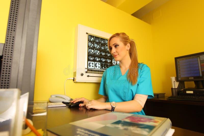 坐在工作书桌的一位微笑的女性医生的画象 免版税库存图片