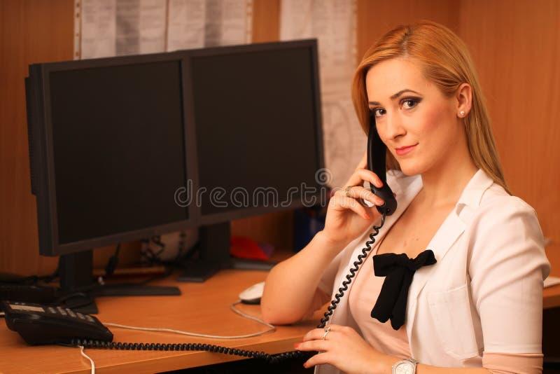 坐在工作书桌的一位微笑的女性医生的画象 库存照片