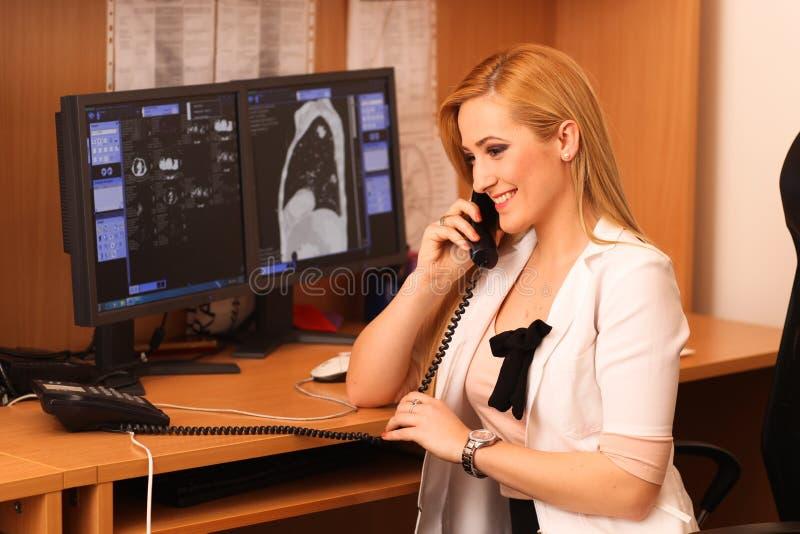 坐在工作书桌的一位微笑的女性医生的画象 库存图片