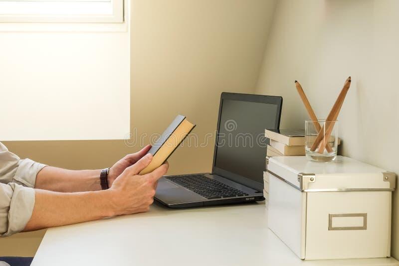 坐在工作场所和看书套的一个人 库存照片
