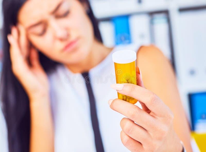 坐在工作场所的年轻病的疲乏的哀伤的妇女拿着有药片的瓶 女性感觉坏在工作 库存图片