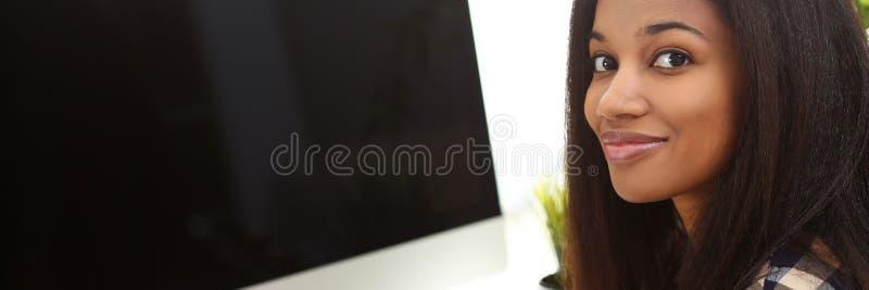 坐在工作场所的黑人微笑的妇女写某事 库存照片
