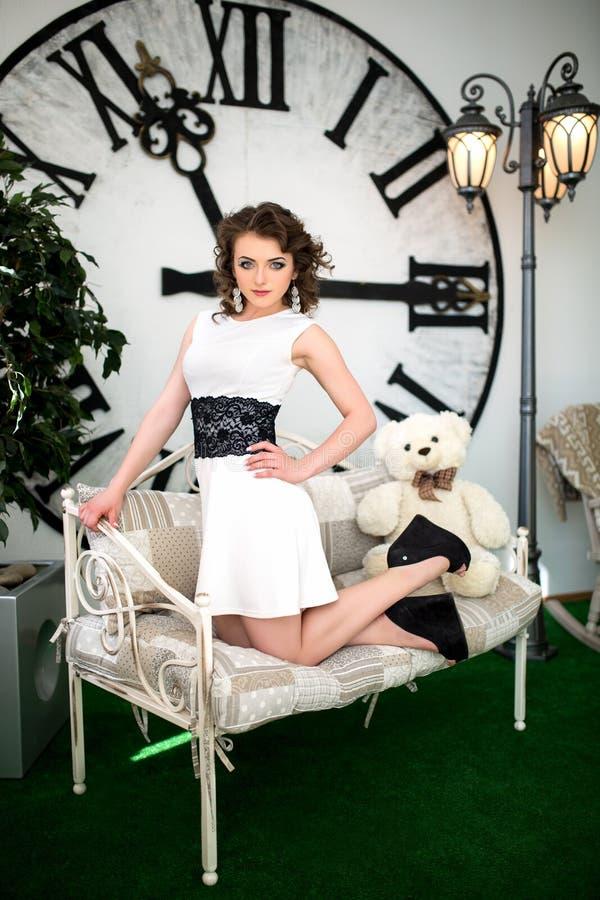 坐在巨大的时钟附近的女孩 图库摄影