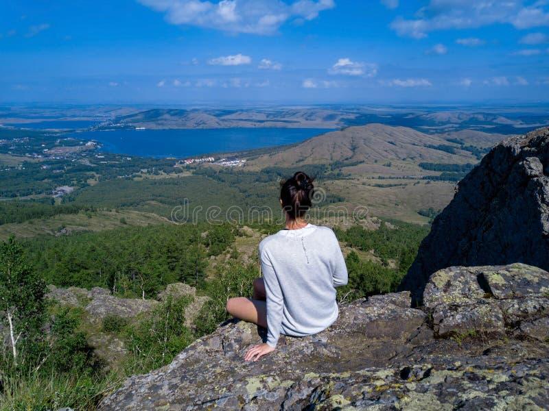坐在巨大的石头边缘的勇敢的女孩 图库摄影