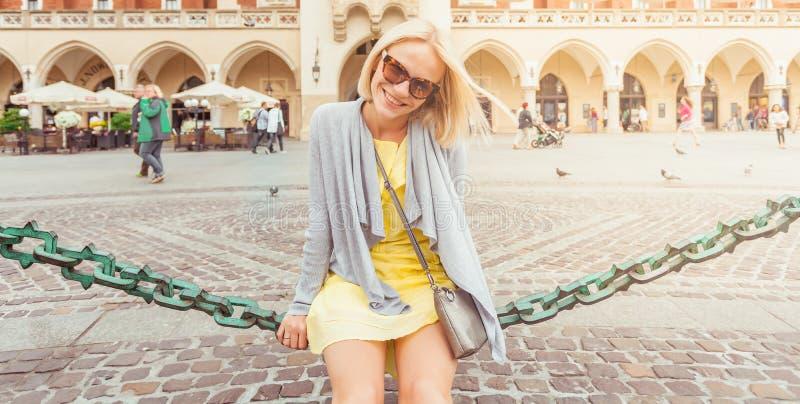 坐在布料霍尔附近的年轻女性游人在克拉科夫的老市中心 免版税图库摄影