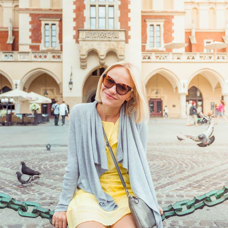 坐在布料霍尔附近的年轻女性游人在克拉科夫的老市中心 图库摄影