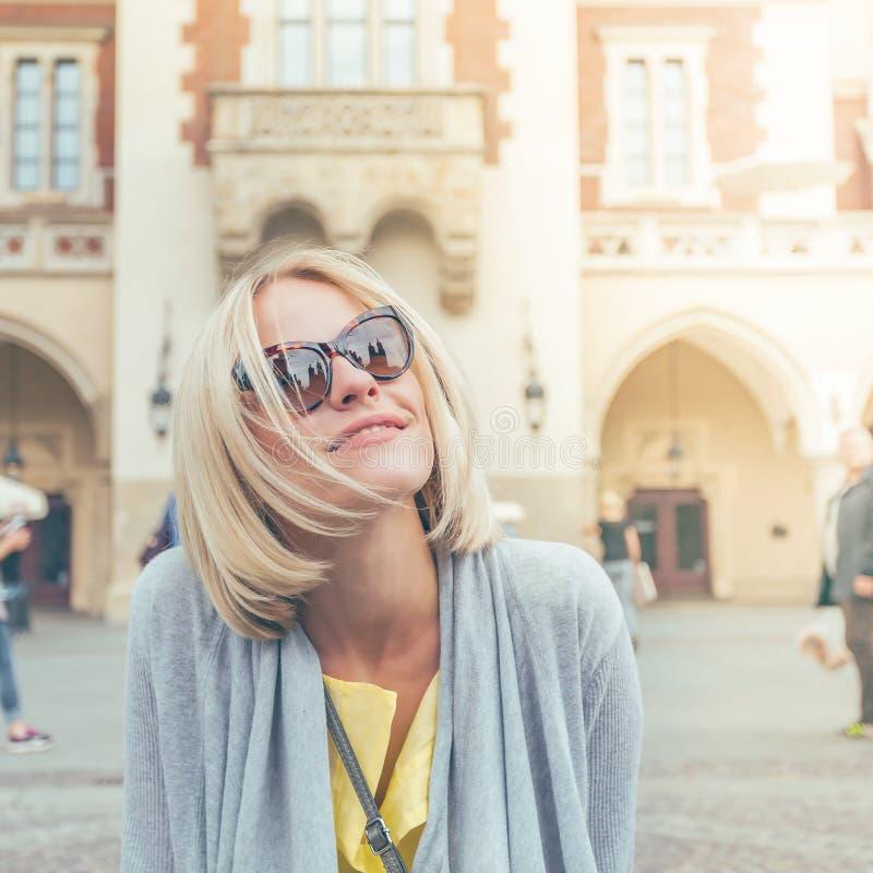 坐在布料霍尔附近的年轻女性游人在克拉科夫的老市中心 免版税库存图片
