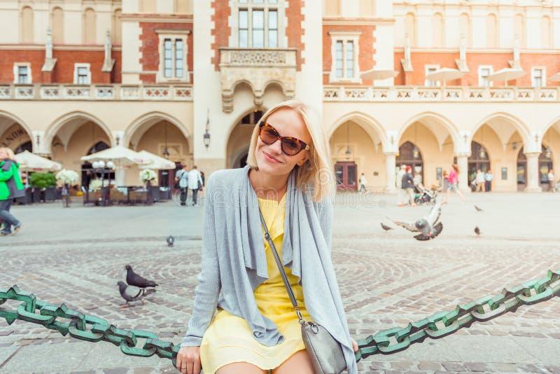 坐在布料霍尔附近的年轻女性游人在克拉科夫的老市中心 库存图片