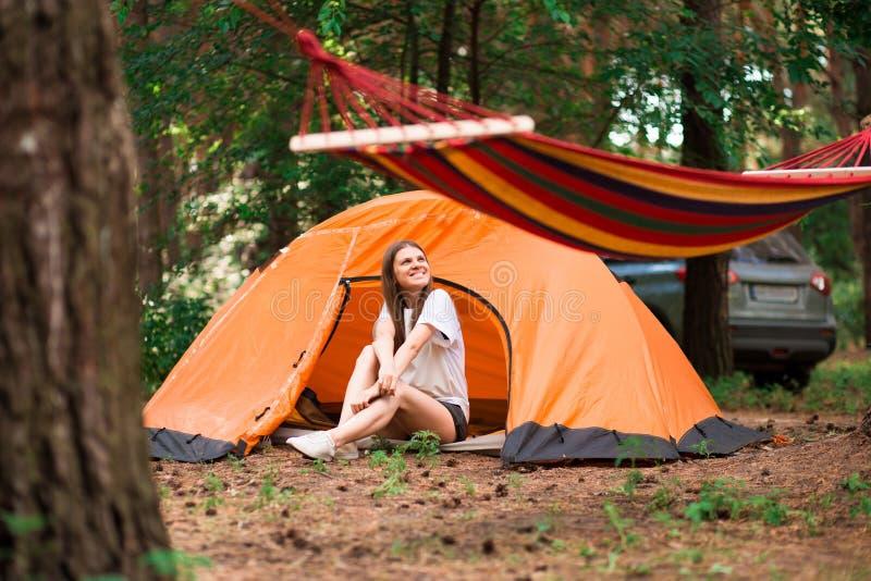 坐在帐篷之外的美女享受远离城市熙来攘往的假日在森林里 免版税库存照片