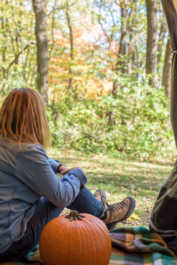 坐在帐篷的妇女用注视着秋天颜色的南瓜 免版税库存照片