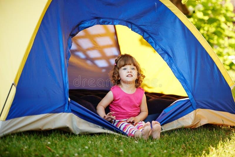坐在帐篷的小美丽的女孩 免版税库存图片