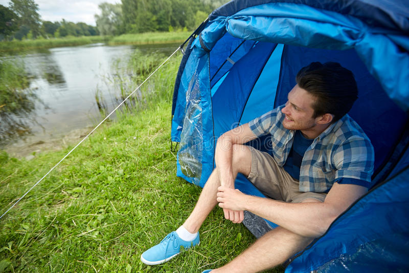 坐在帐篷的愉快的年轻人在野营 库存图片