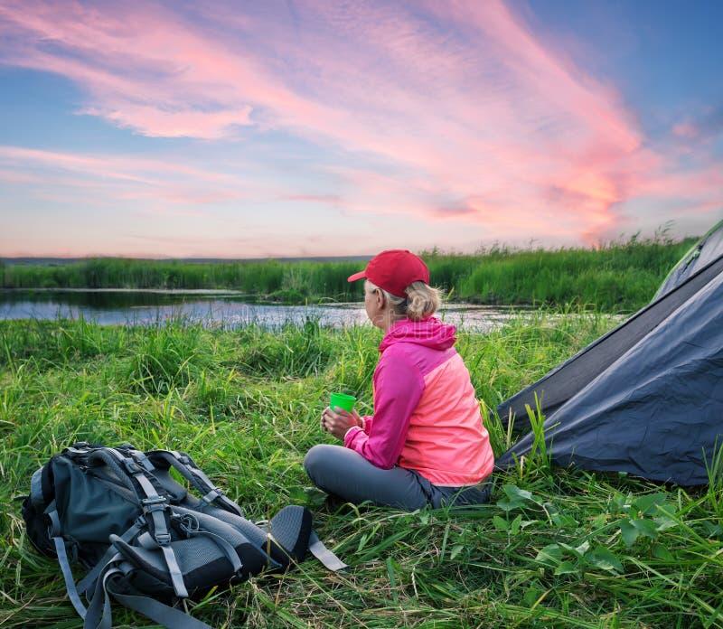 坐在帐篷附近的女孩看黎明 免版税图库摄影
