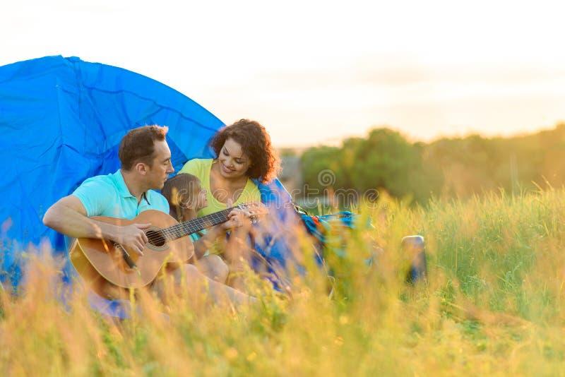坐在帐篷附近的愉快的家庭 图库摄影