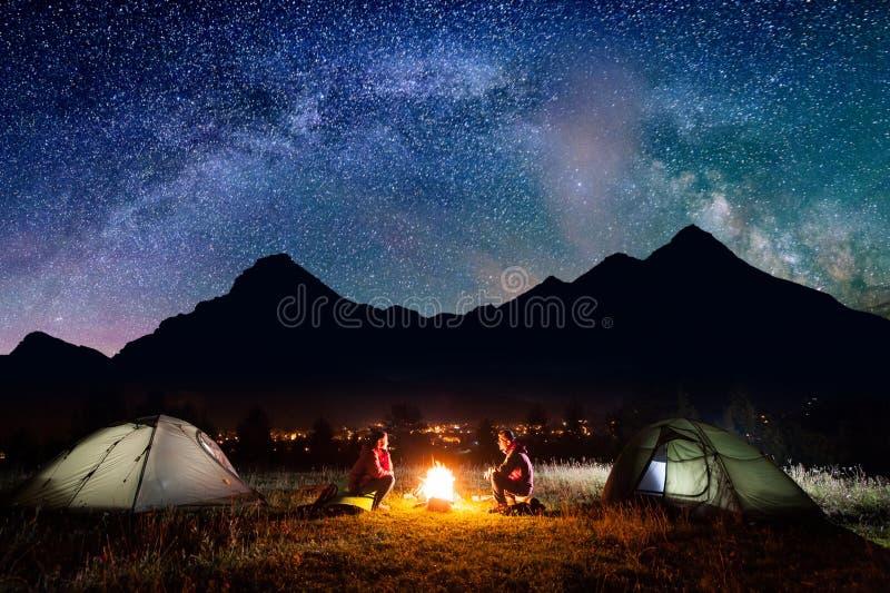 坐在帐篷附近的男人和妇女在晚上 免版税库存照片