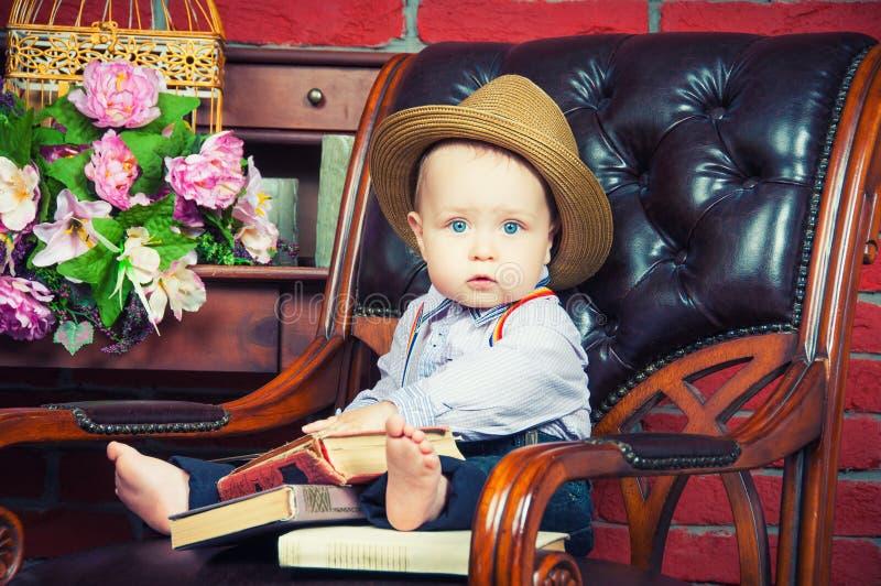 坐在帽子的一个皮椅的小绅士 免版税库存照片