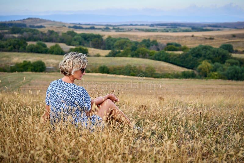 坐在干燥贫瘠草的妇女看  免版税库存图片