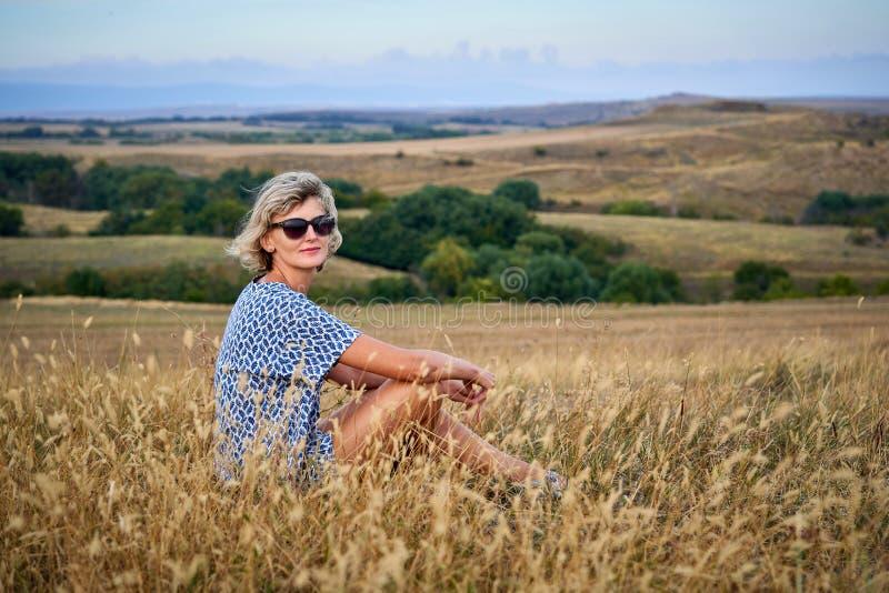 坐在干燥贫瘠草的妇女,看照相机 图库摄影