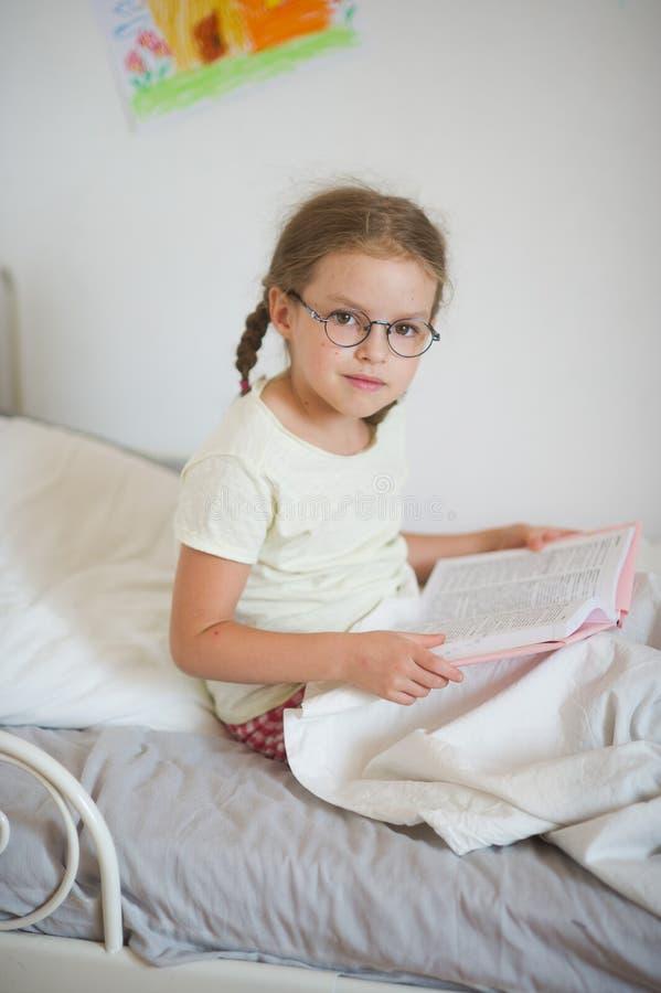 戴坐在床上和拿着一本开放书的眼镜的小女孩 免版税库存照片