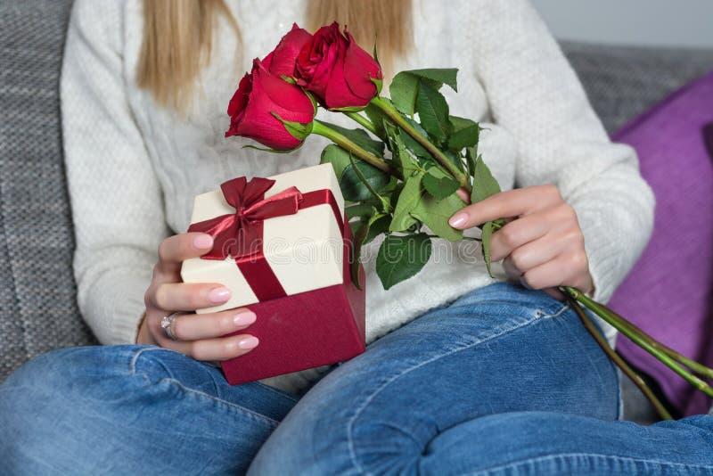 坐在床上和拿着红色玫瑰和礼物盒在手上的女孩在腿 库存照片