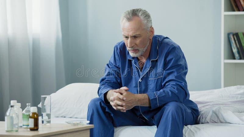 坐在床上和看药片、疗程和医疗保健的哀伤的老人 库存照片