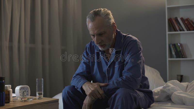 坐在床上和遭受失眠,健康的沮丧的资深人 库存图片