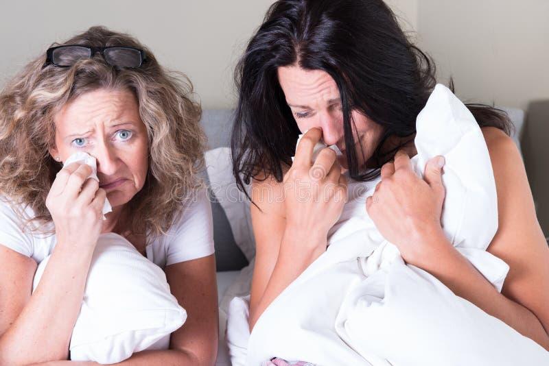 坐在床和哭泣上的两名可爱的妇女 免版税库存图片